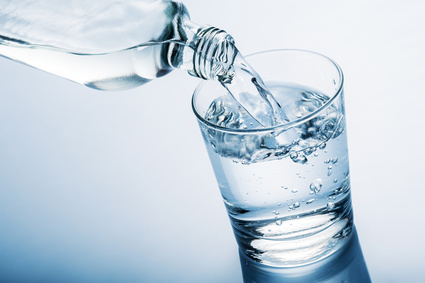 pouring water into glass from a bottle, on blue background